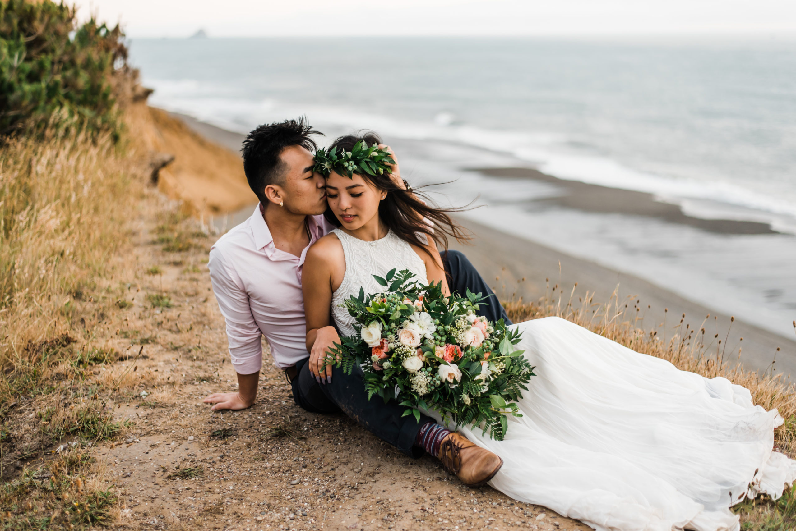 elopement couple sitting together on a cliff overlooking the ocean